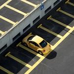 gelbes Fahrzeug alleine auf Parkplatz